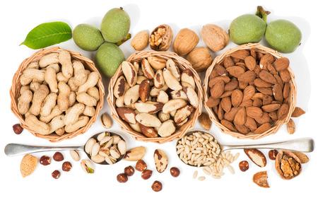 Assortiment noten in een rieten kom geïsoleerd op een witte. Van bovenaf te bekijken.