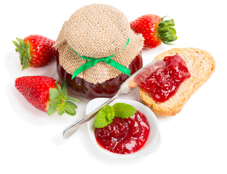 strawberry jelly: Strawberry jam in a glass jar, in a bowl, over toast and fresh berries  isolated on white