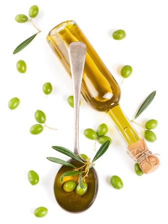 Olive oil in a glass bottle and green olives isolated on white, top view.