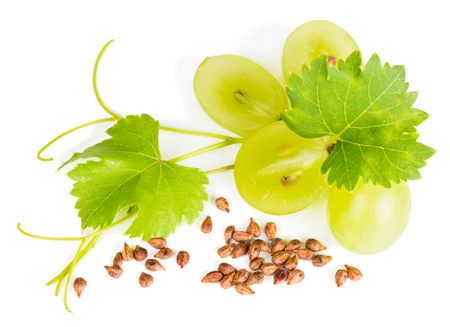 Top view of yellow grapes, grape seeds and vine isolated on white. Selective focus on a seeds.