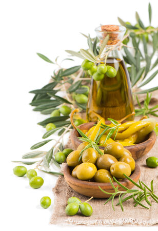 Appetizer of olives with chili pepper and olive oil  on a linen tablecloth,  decorated by fresh olives with leaves. Isolated on white background. photo