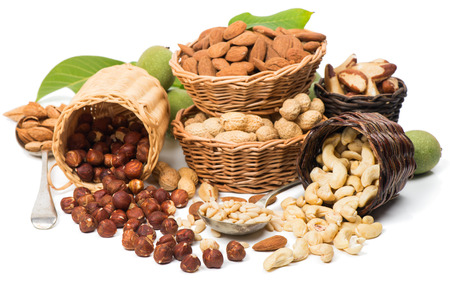 Variety  nuts  (shelled and in their shells)  including almonds, cashew, hazelnuts, brazil nuts, peanuts, green walnuts with leaves and pine nuts.  Isolated on white background  스톡 콘텐츠