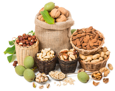 frutas secas: Diferentes frutos secos en un canastas aisladas sobre fondo blanco
