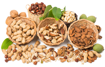 View from above of varieties of nuts: peanuts, hazelnuts, cashew, walnuts, pistachio, brazil and  pine nuts isolated on white background  photo