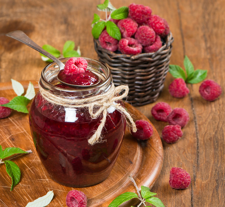 closeup of jar of raspberry jam with fruits on wooden table photo
