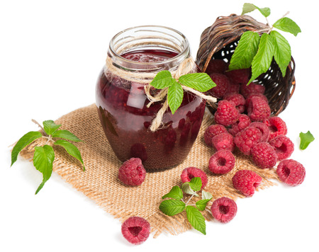 Raspberry jam in a jar tied with a rope and fresh berries in a  basket is scattered, isolated on white background. photo