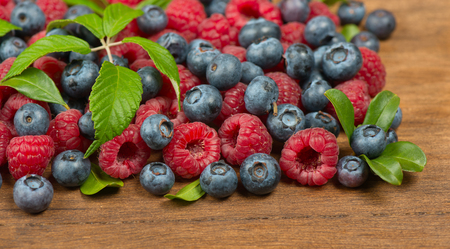 mixed fruits: ripe of berries with green leaves on wooden table -  raspberry and blueberry  Stock Photo