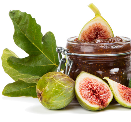 Jar with fig jam and fresh fruits with leaves in front isolated on white background  photo