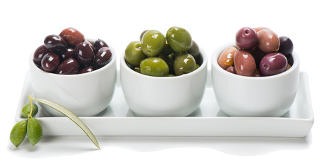 Assortment of olives in a white  bowls  isolated on white photo