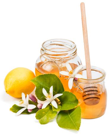 blossom honey: jars of azahar honey, lemon, flowers and honey dipper isolated on white