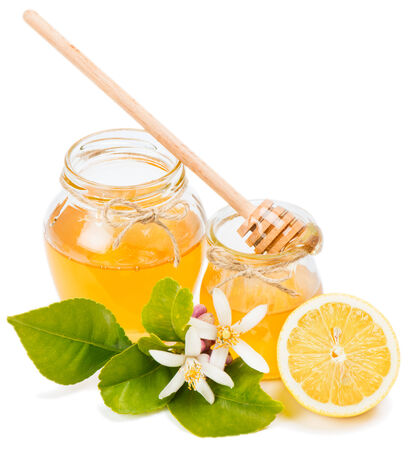 blossom honey: Honey in glass jars with fruit and flowers of lemon isolated on white background Stock Photo
