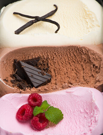 neapolitan: background of the surface texture of scoop of fresh creamy frozen  ice cream of vanilla,  raspberry and    chocolate Stock Photo