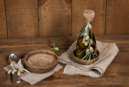 Rustic table setting and olives on old wooden table photo