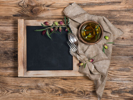 blackboard for menu on wooden table with olives, olive oil , knife and fork  over wooden table photo