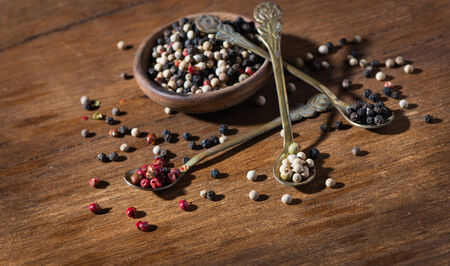 Colored pepper in the wooden bowl, on the wooden background photo