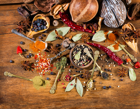 pepper flakes: Top view of different spices and herbs in a metal spoons over wooden background