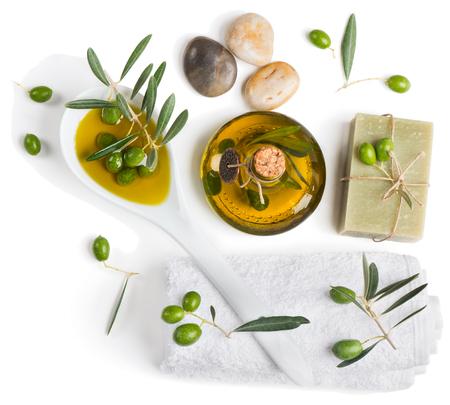 rama de olivo: Spa y bienestar ajuste con piedras zen, aceitunas y una toalla sobre fondo blanco, vista desde arriba Foto de archivo