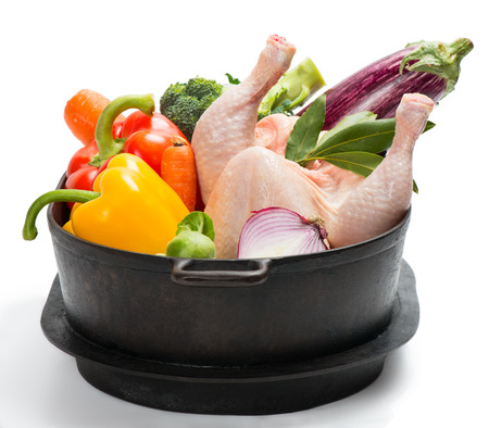 Raw chicken with vegetables in a saucepan isolated on white photo