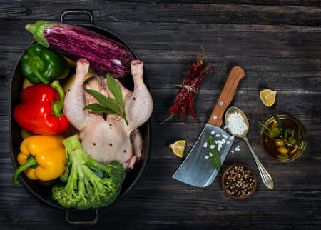 uncooked chicken with vegetables in a black casserole on a old black wooden table  top view Stock Photo