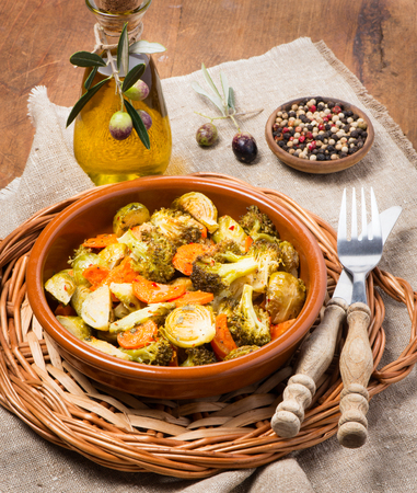 ovenbaked: Oven-baked vegetable (brussels sprouts, carrots, broccoli) served with olive oil and spices on wooden table.
