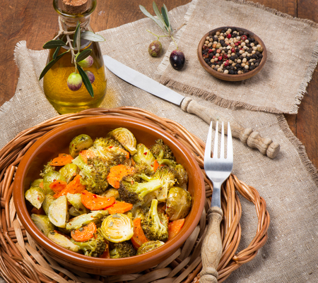 ovenbaked: Oven-baked vegetable (brussels sprouts, carrots, broccoli) served with olive oil and spices on a wooden table.