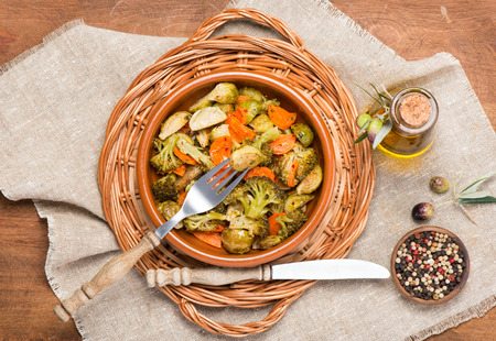 ovenbaked: Above view from oven-baked vegetable (brussels sprouts, carrots, broccoli) served with olive oil and spices on wooden table.
