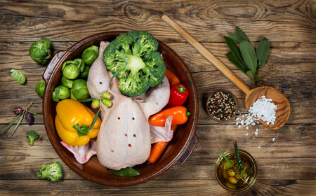 uncooked chicken with vegetables in a pan on a old rustic wooden table, top view photo