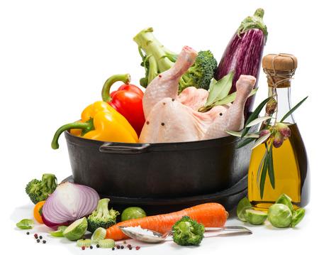 Rauwe kip met groenten en kruiden in een zwarte braadpan op wit wordt geïsoleerd.