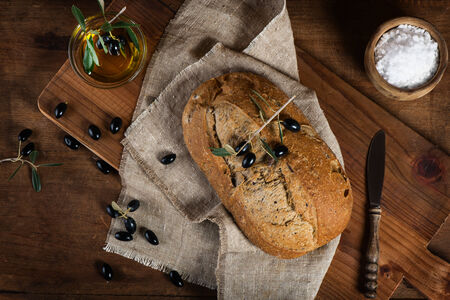 wholemeal: Olive bread, black olives and olive oil on a rustic wooden background, top view Stock Photo