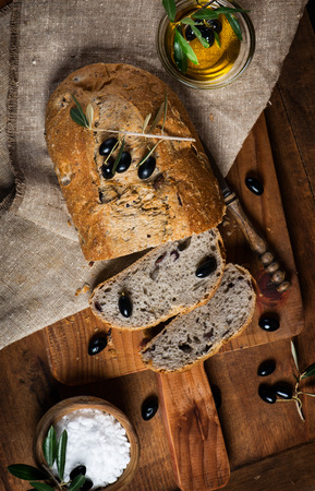 Sliced olive bread, black olives and olive oil on a rustic wooden background photo