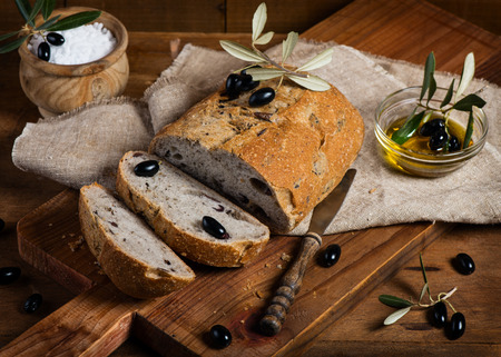 Sliced olive bread of wholemeal, black olives and olive oil on a rustic wooden background photo
