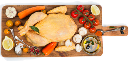 Whole raw chicken with spices and vegetables on a old wooden cutting board, isolated over a white background, top view photo