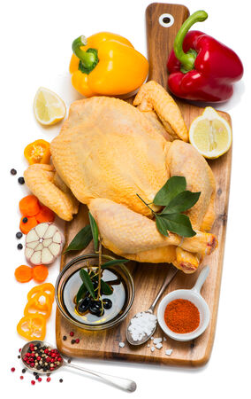Whole raw chicken with spices and vegetables on a wooden cutting board, isolated over a white background, top view photo