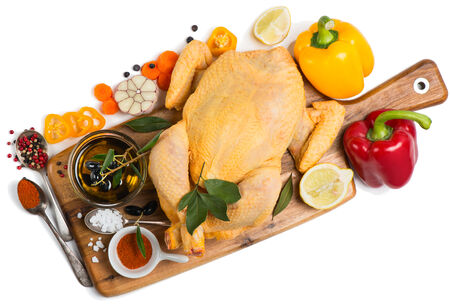 Uncooked chicken with spices and vegetables on a wooden cutting board, isolated over a white background, top view photo