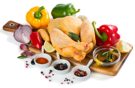 Whole raw chicken with spices and vegetables on a wooden cutting board, isolated over a white background photo
