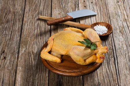 Whole raw chicken on a old wooden  background with copy-space Stock Photo