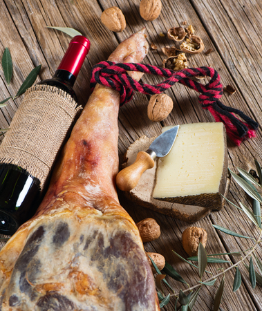 aperitive: whole leg of ham, bottle of red wine, cheese, walnuts and twig of olive tree on a old wooden background, top view Stock Photo