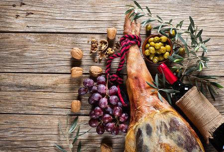 훈제 햄의 다리 전체, 텍스트를위한 공간, 상위 뷰와 오래 된 나무 배경에 레드 와인, 포도, 호두, 절인 올리브의 병