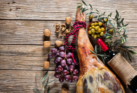 whole leg of smoked ham, bottle of red wine, grapes, walnuts and pickled olives on a old wooden background with space for text, top view