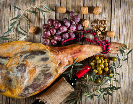 whole leg of smoked ham, bottle of red wine, grapes, walnuts and pickled olives on a old wooden background