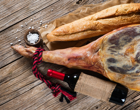 aperitive: whole leg of smoked ham, bottle of red wine, bread and salt on a old wooden background, top view