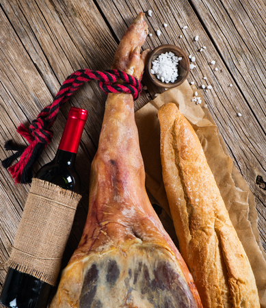 whole leg of smoked ham, bottle of red wine, bread and salt on a old wooden background, top view photo
