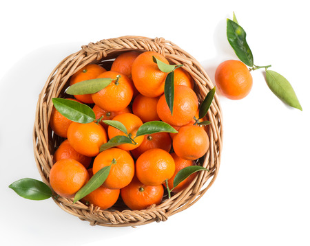 mandarin orange: Ripe tangerine with leaves in a basket, isolated on white, top view