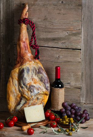 aperitive: Jamon serrano, olives, wine, cheese, tomatoes and grapes on a wooden old background