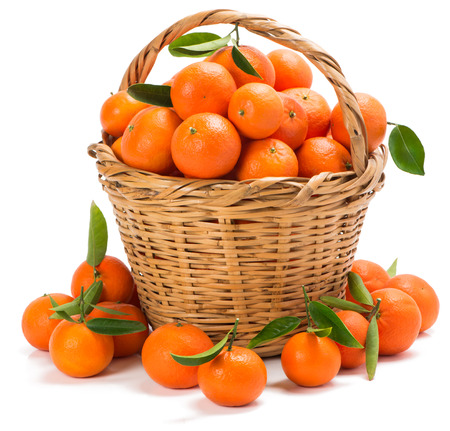 tangerines with green leaves in a basket with handle, some on the surface in the foreground isolated on white
