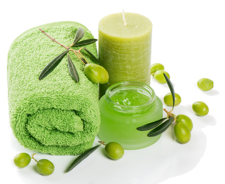 spa candle: Spa setting of green olive: cream, towel, candle and twigs of olive tree isolated on white background.