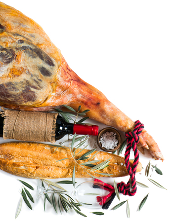 whole leg of smoked ham, bottle of red wine, bread and salt isolated on white, top view photo