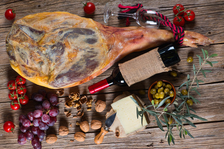 Cured ham leg, spanish tapas, glass and bottle of red wine top view on a wooden background photo