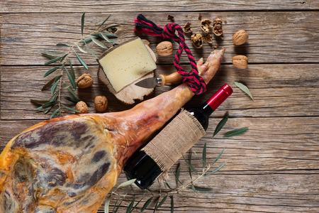 나무 오래 된 배경에 햄 다리, 치즈, 호두와 레드 와인 상위 뷰의 병을 치료