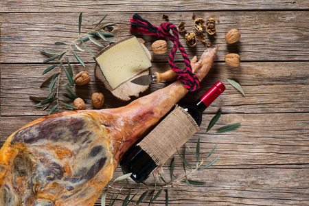 Cured ham leg, cheese, walnuts and bottle of red wine top view on a wooden old  background Standard-Bild
